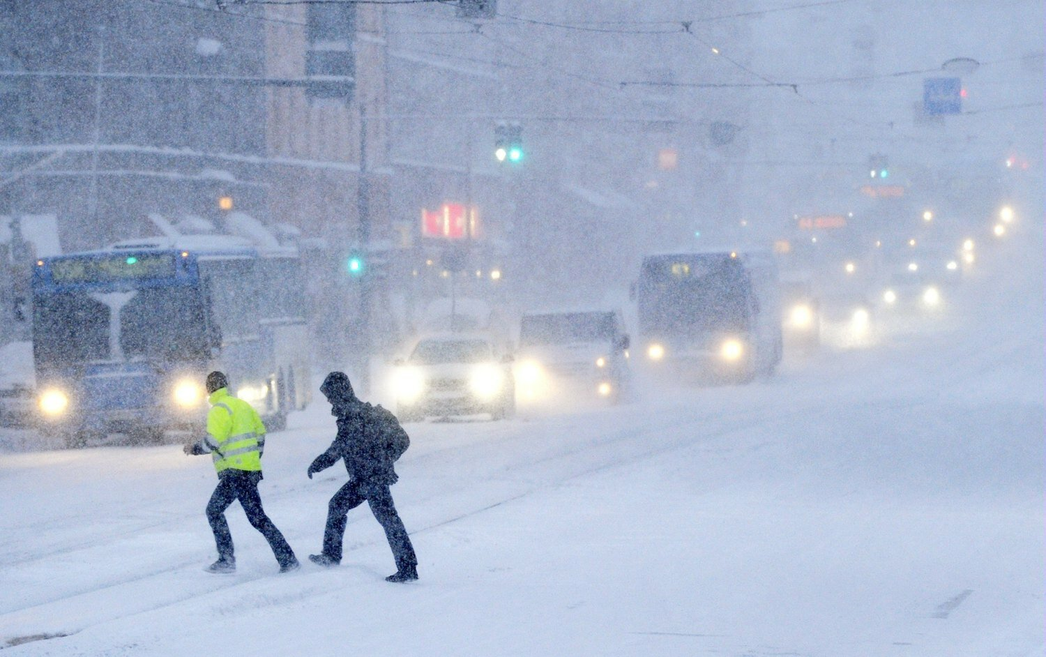 People cross a snow covered road on February 3, 2012 in Helsinki. Temperatures plunged to new lows in Europe where a week-long cold snap has now claimed more than 220 lives and forecasters warned that the big freeze would tighten its grip at the weekend. AFP PHOTO / LEHTIKUVA / Vesa Moilanen *** FINLAND OUT ***